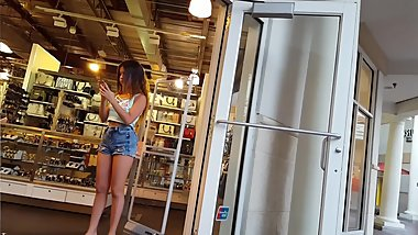 Candid voyeur teen with belly ring in short shorts