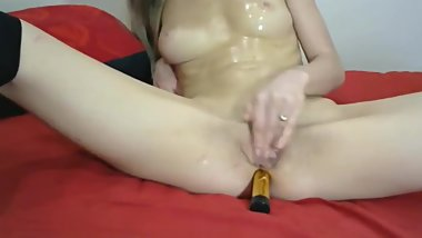 girl in oil with a dildo in her ass fingering clit