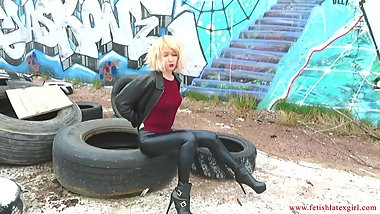 German skinny blonde walks in leather pants and high heels.